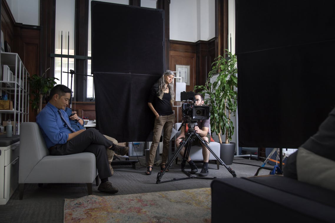 Woman with long gray hair stands next to a seated man with brown hair, they both are watching a viewfinder on a video shoot.  On the left are two actors sitting on a couch and looking at their phones.