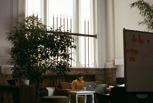 Woman in yellow sweater sits alone on a couch working on her laptop