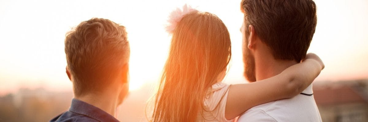 Gay same-sex couple looking at the sunset with her adopted or foster child.