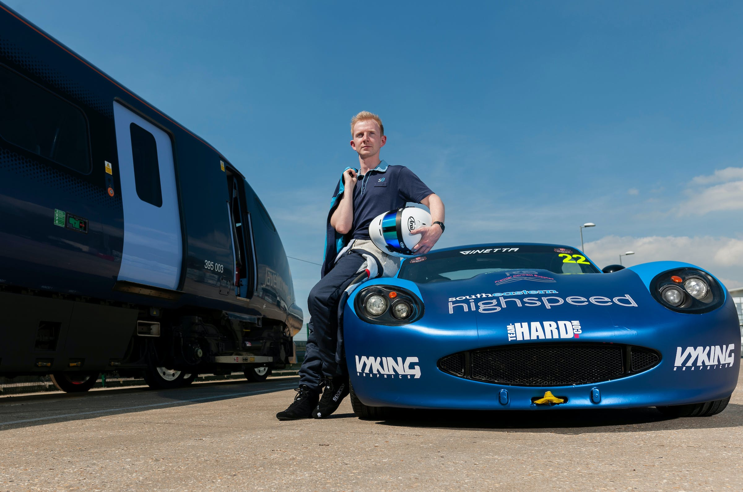 Toby Trice sitting on the hood of his racing car, parked adjacent to a train.