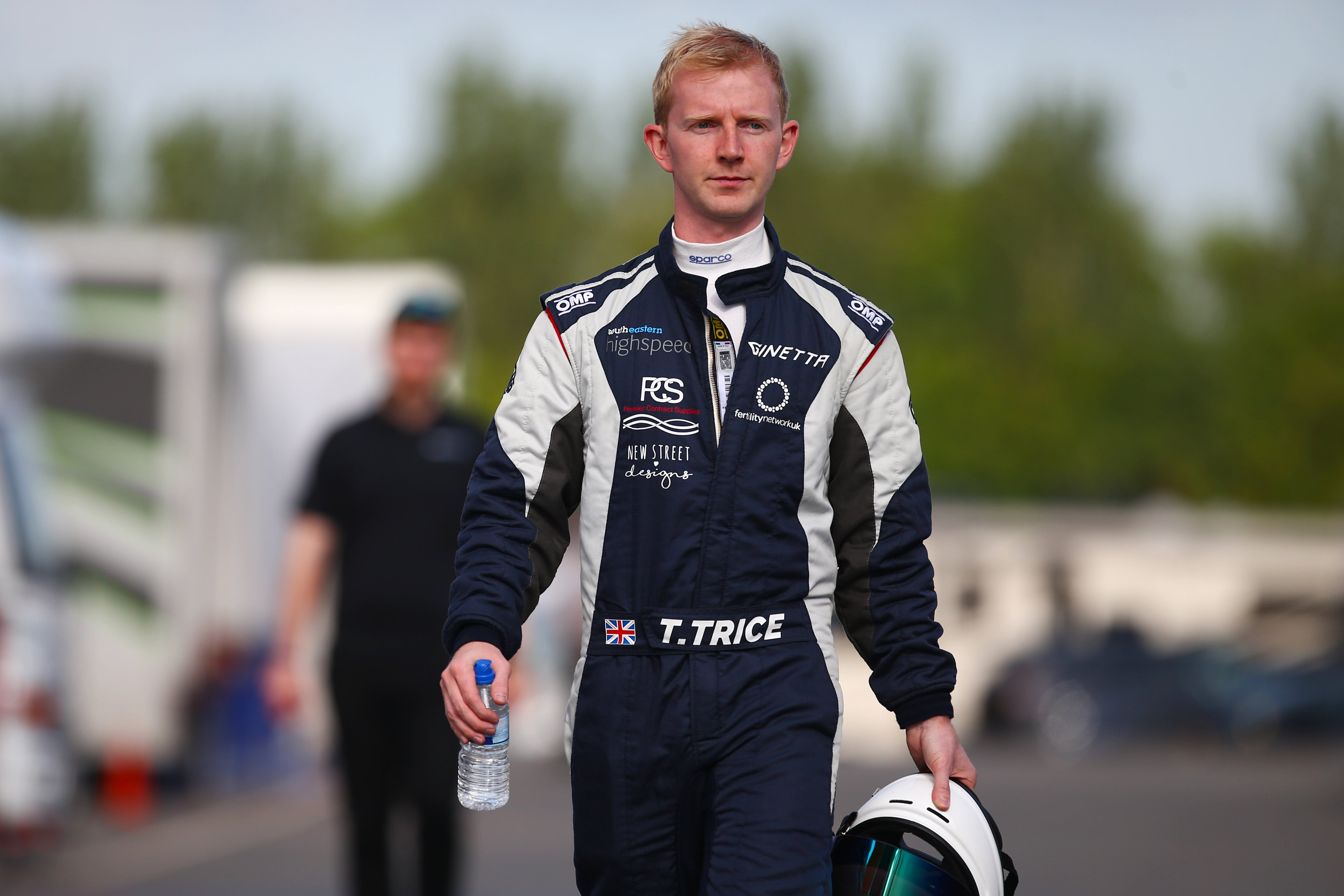 Toby Trice in his racing gear, holding the helmet in his hand, bottle of water in another, walking towards the camera.