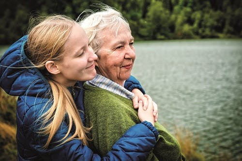 A younger woman standing behind an older woman and hugging her. Both are smiling and there is a lake behind them.