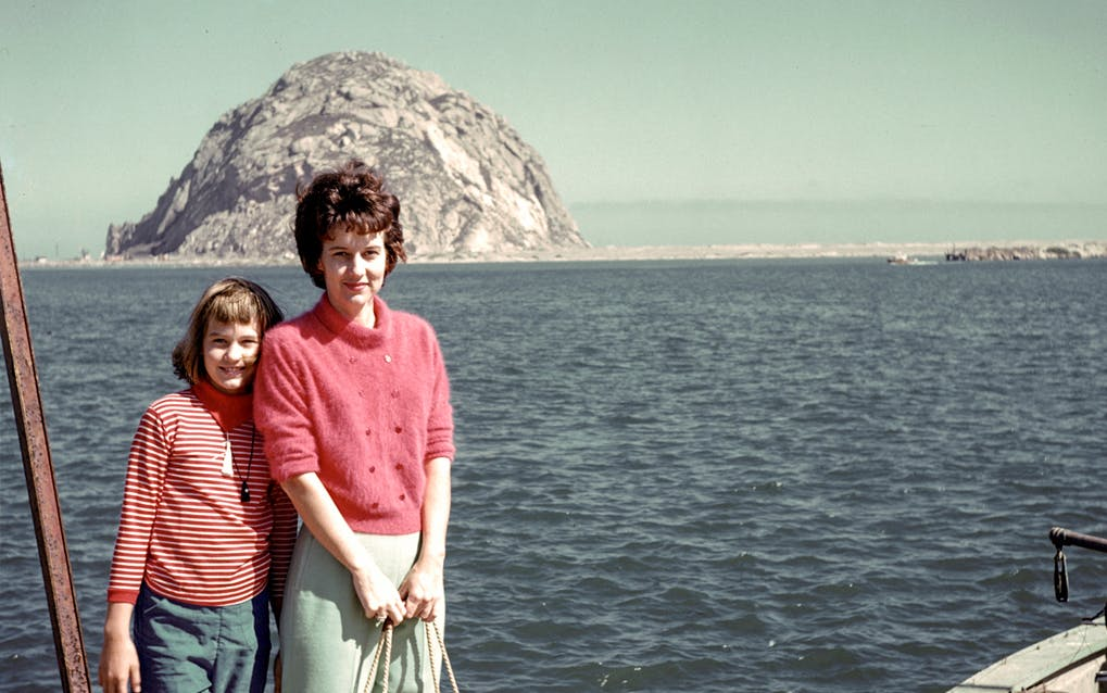 A girl and woman, both wearing pink tops, standing on the deck of a boat and looking straight at the camera. There is a big rock in the background.