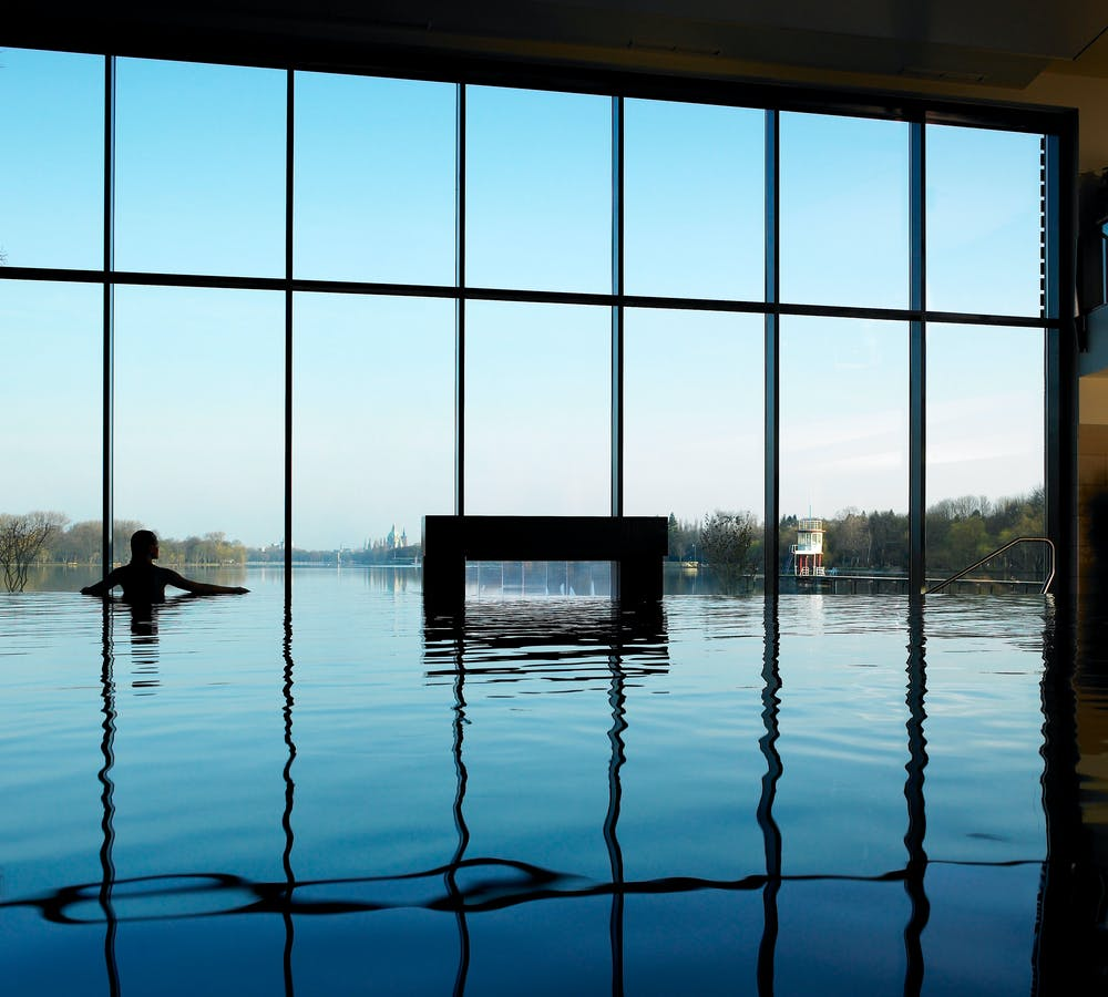 Women standing in the indoor pool staring out onto the lake