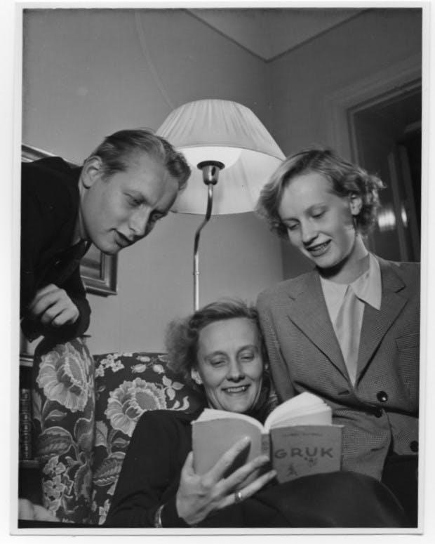 Lasse, Astrid och Karin tittar i en bok