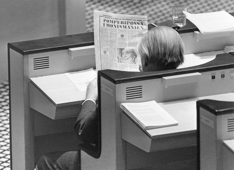 """Finansminister Gunnar Sträng sitter i sin riksdagsbänk och läser Astrid Lindgrens """"Pomperipossasaga"""" införd i Expressen 10 mars 1976."""