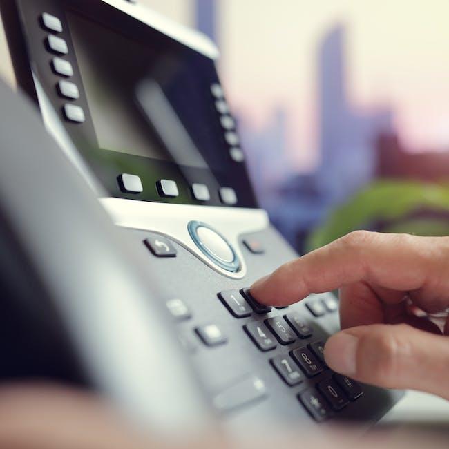 Ręka wybierająca numer na stacjonarnym telefonie Cisco
