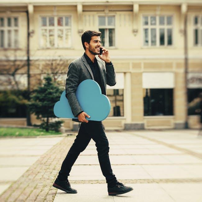 Mężczyzna idący i rozmawiający przez telefon, niosący w ręku niebieską chmurę