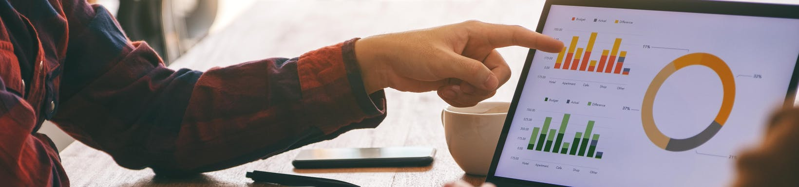 Kobieta wskazująca palcem na laptopa, na którego ekranie widać aplikację do prezentowania danych, wykresy