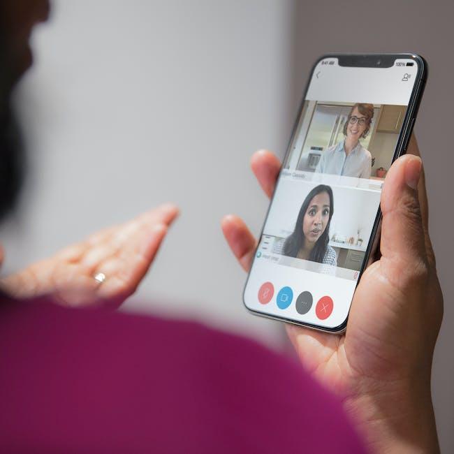 Telefon wykorzystywany przez kobietę do udziału w widekonferencji, spotkaniu, z zainstalowanym systemem do wideokonferencji