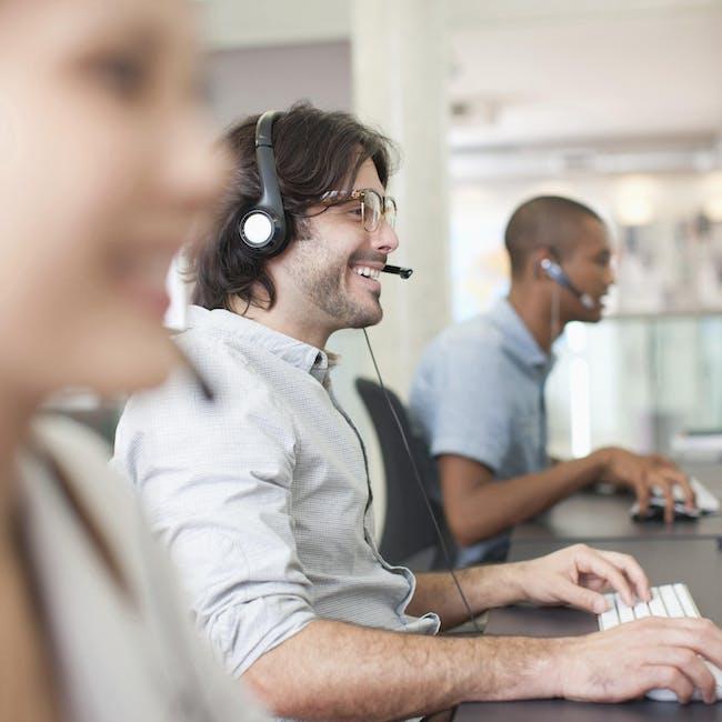 Zespół osób pracujących przy komputerach z słuchawkami na uszach, profesjonalne wsparcie IT