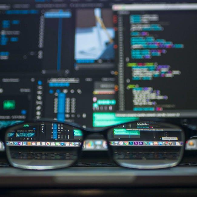 Okulary leżące przez ekranami monitorów, na których widać kody programistyczne