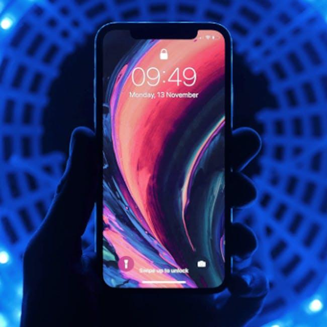 Ręka trzymająca smartfon z tapetą w żywych, kontrastowych kolorach