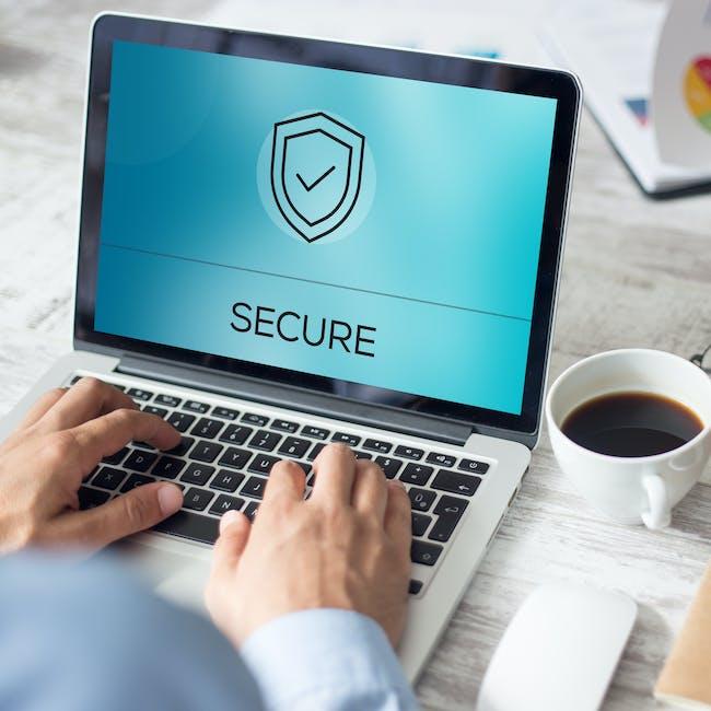 Osoba pracująca przy laptopie, na ekranie komputera widoczny napis secure