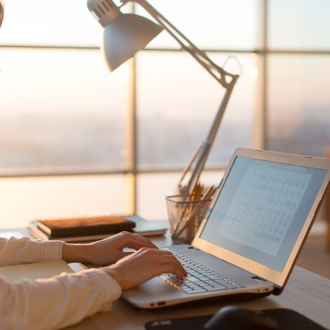 Osoba pracująca przy laptopie, wykonująca pracę zdalną
