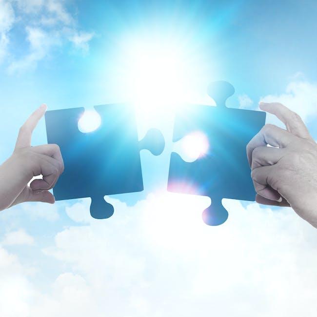 Dwa pasujące do siebie puzzle na tle nieba i chmur