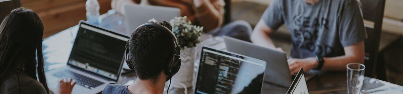 Zespół IT pracujący przy laptopach