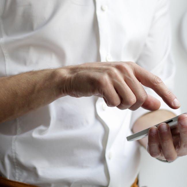 Mężczyzna w białej koszuli klikający na ekran smartfona