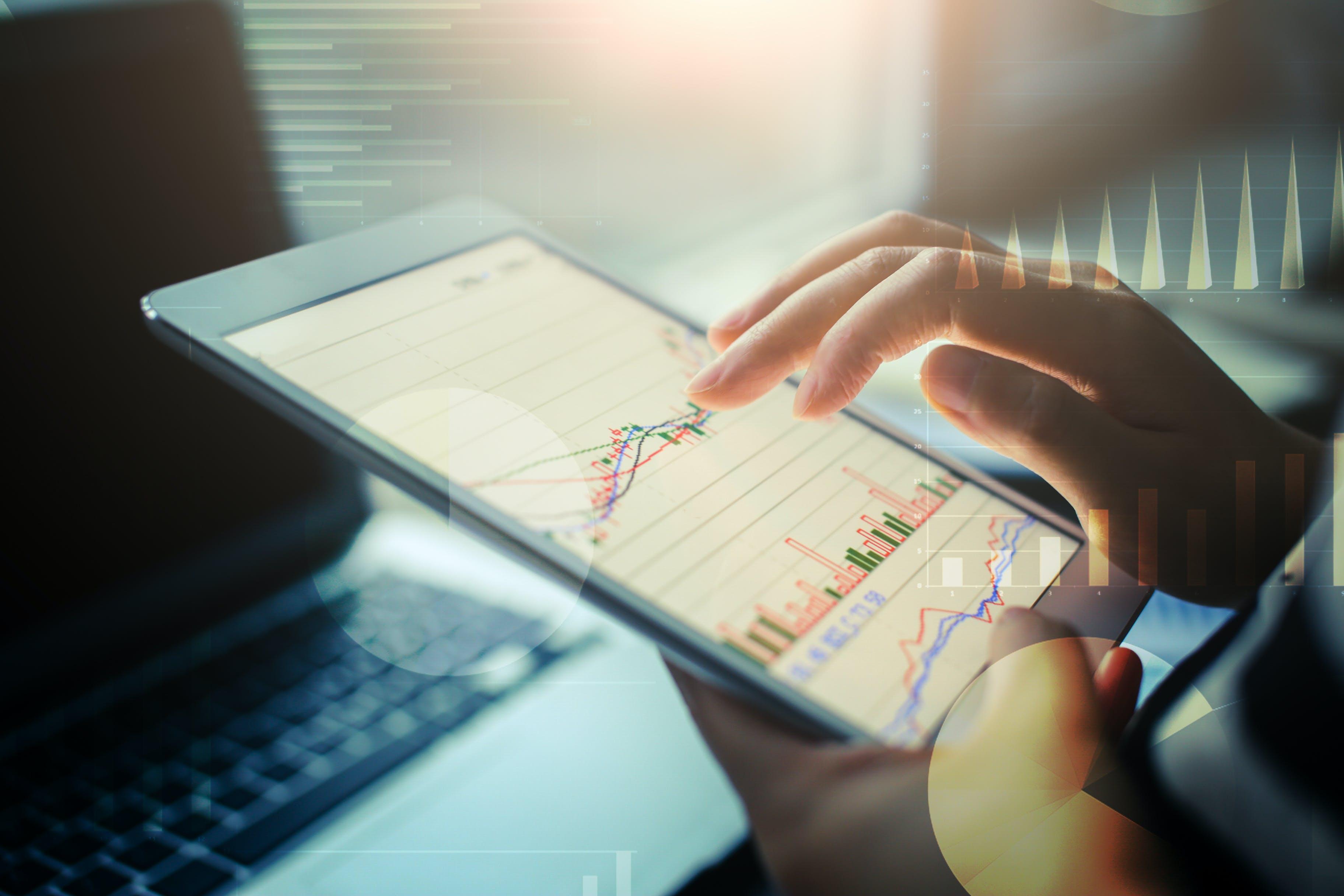 Osoba przeglądająca na tablecie wykresy, cyfrowe dokumenty