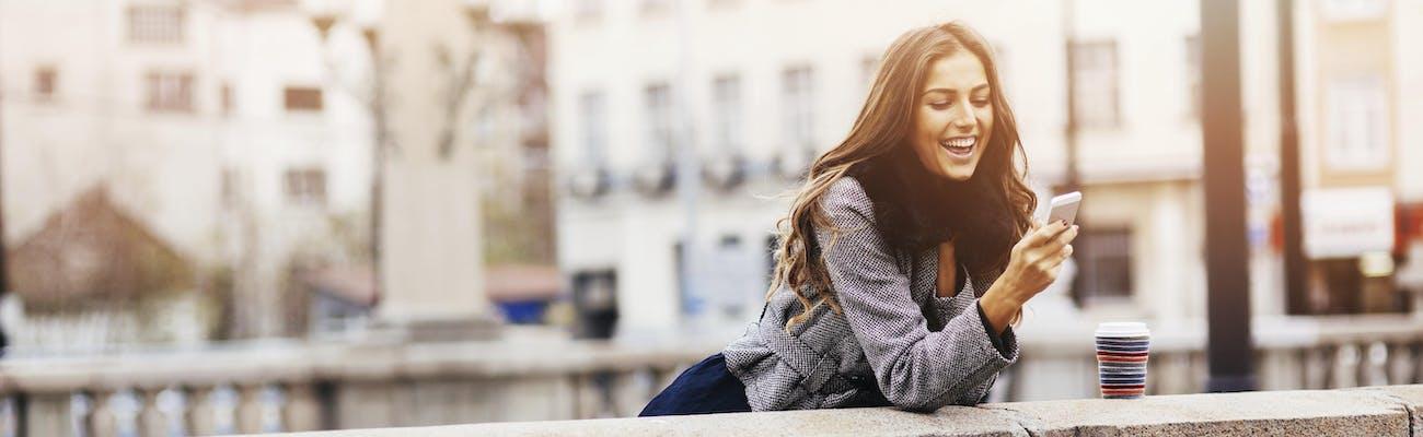Uśmiechnięta kobieta trzymająca telefon