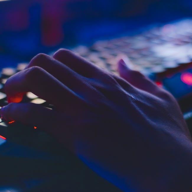 Ręka na klawiaturze wykonująca działania związane z phishingiem