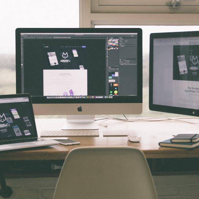 Stanowisko pracy projektanta, programisty z trzema ekranami na których widoczne są projekty stron www, projekty graficzne