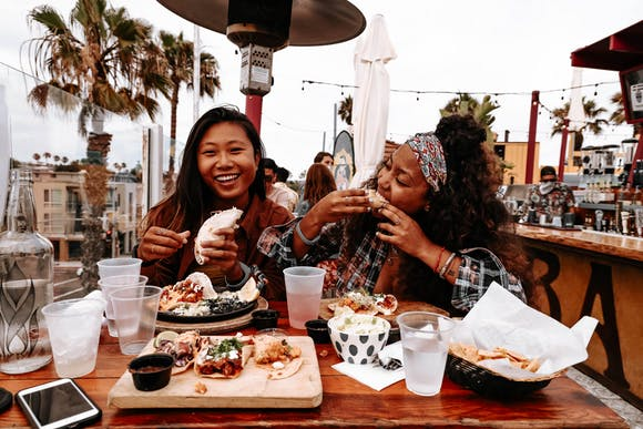 Two women eating at a table outdoors and smiling.