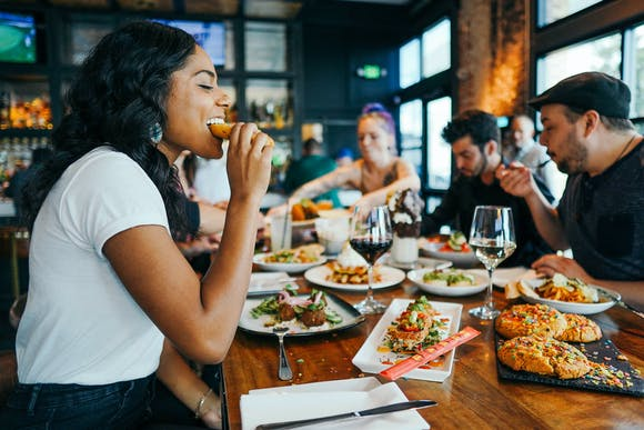 A woman at a table with friends, taking a bite of food.