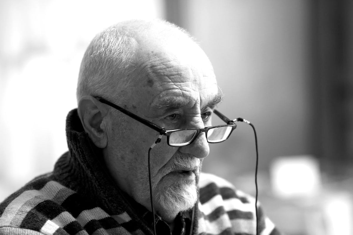 Older caucasian man with black glasses sitting on the ridge of his nose