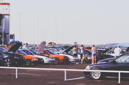 Cars with hoods open at an outdoor show
