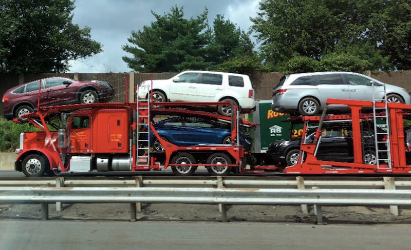 A car trailer carrier transporting several vehicles