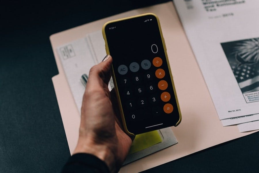 Hand holding an iPhone with the calculator app displaying a zero