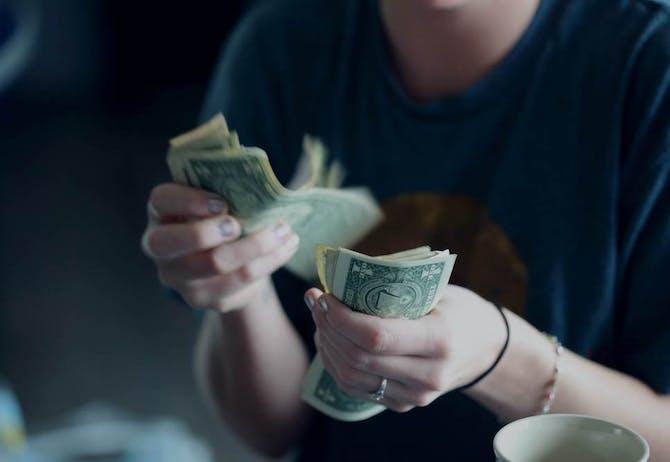 Woman counting US dollar bills