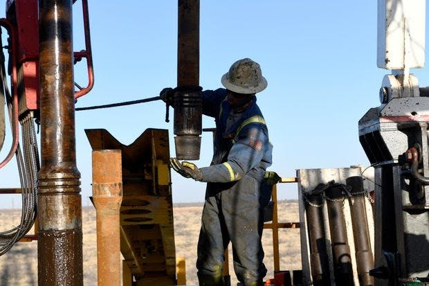 A worker drills for oil