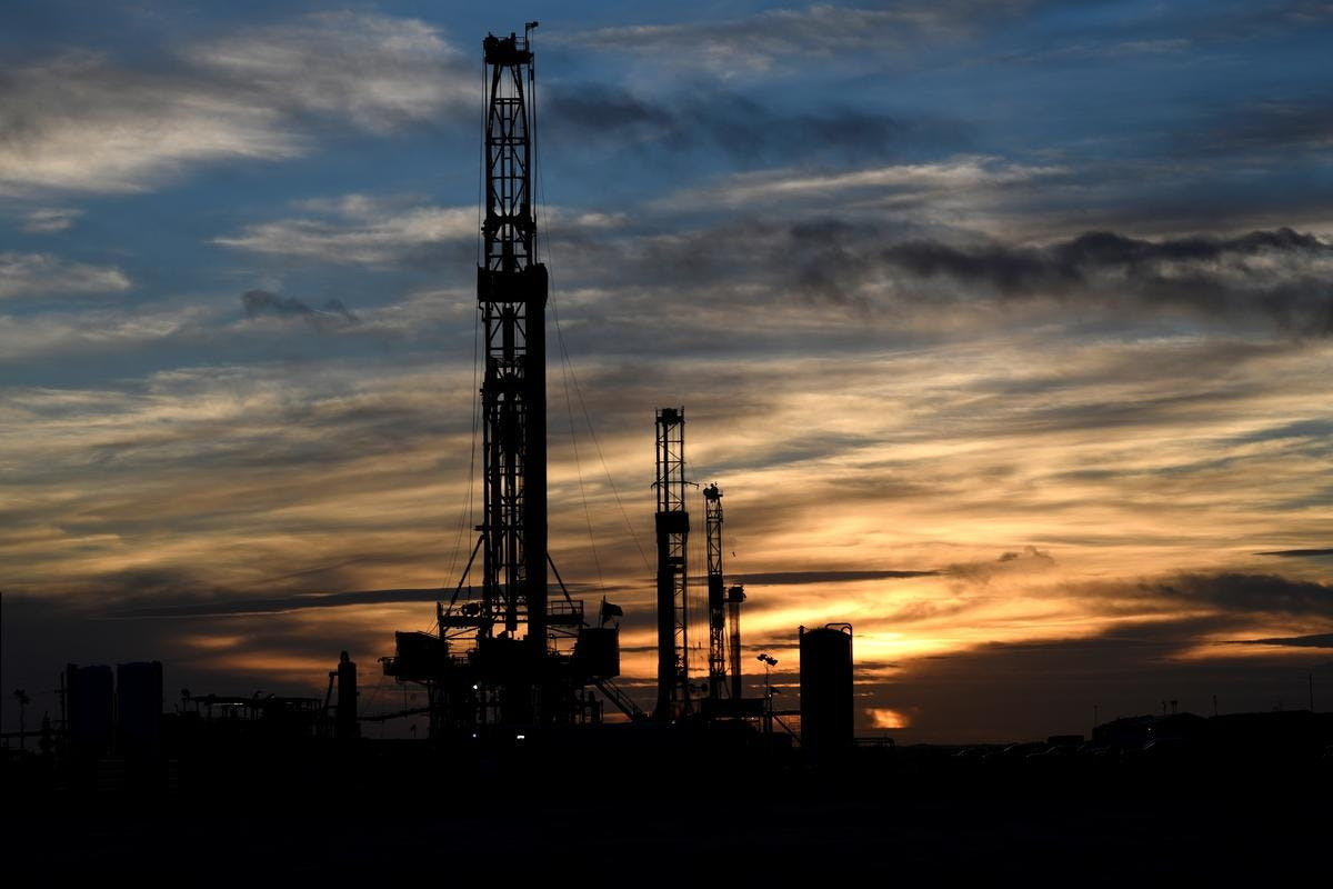 Drilling rigs operate at sunset in Midland, Texas U.S.