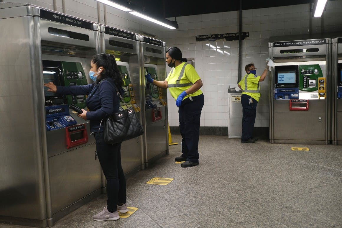As a commuter buys a fare, MTA employees clean the machines in New York, Monday, June 8, 2020.