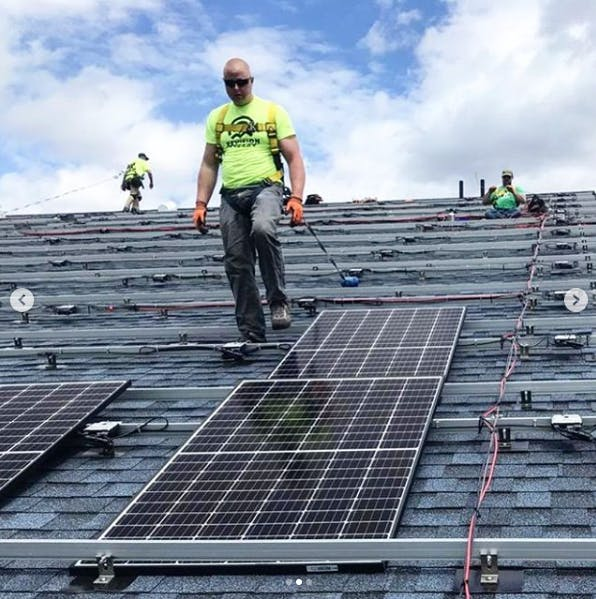 A ReVision Energy worker installs solar on the roof of Badger Balm in Gilsum, New Hampshire in May 2020.