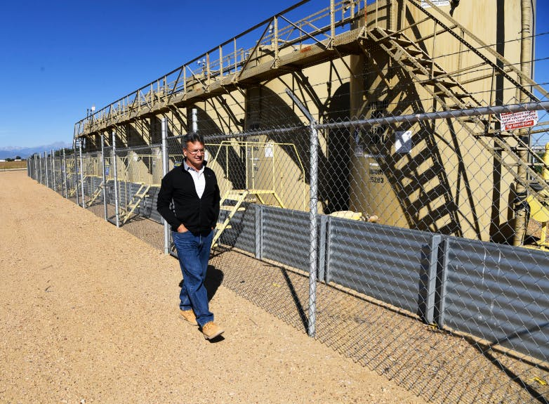 Farm owner Mark Schell walks next to tank batteries from a non-productive well on his 310-acre farm in Longmont on Sept. 02, 2020.