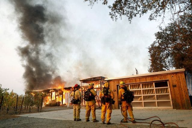 A group of firefighters look on as a house burns during the wind-driven Kincade Fire in Healdsburg, California