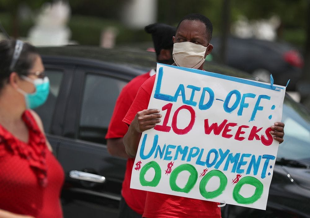 Protestor holds sign about unemployment