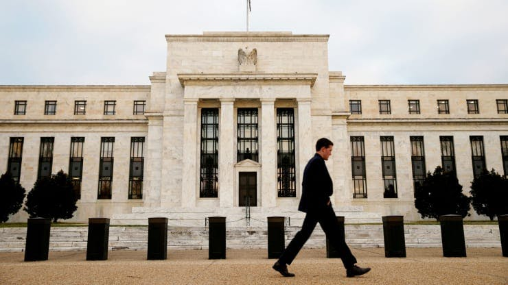 Man walks in front of the Federal Reserve building