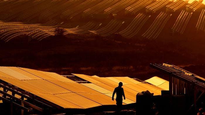 Worker walking solar panel field sunset