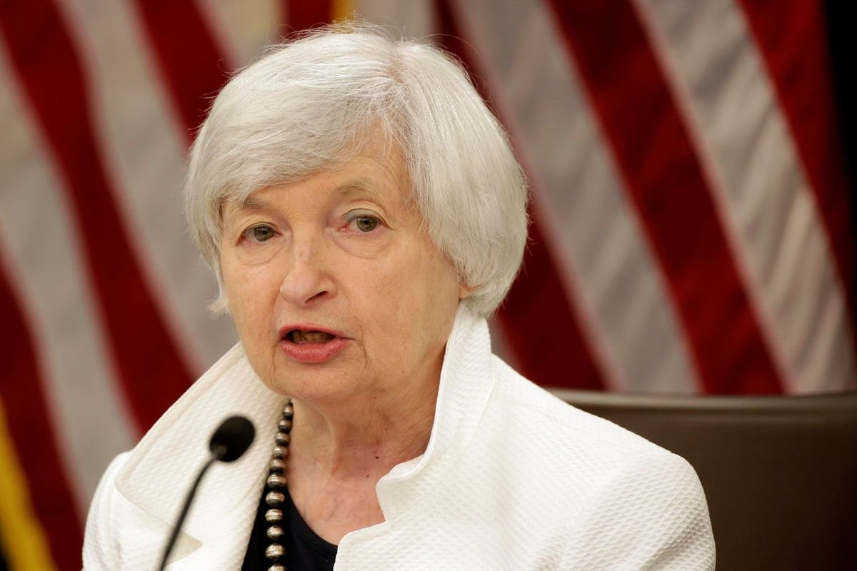 Treasury Secretary Janet Yellen talking into a microphone with flags behind her