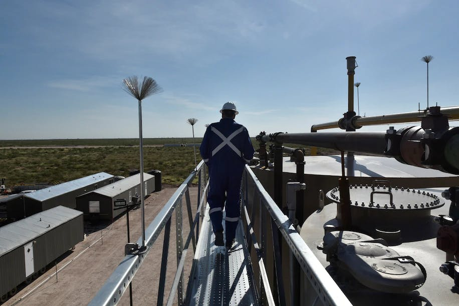 John Lee, a manager at Oasis Petroleum, walks atop a new oil production facility in Texas in 2018
