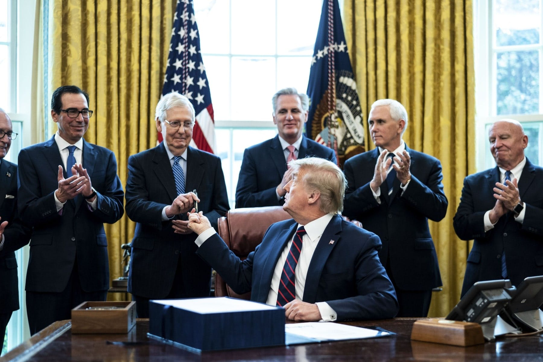 President Donald Trump hands a pen to Senate Majority Leader Mitch McConnell (R-Ky.) after signing the Cares Act on March 27.