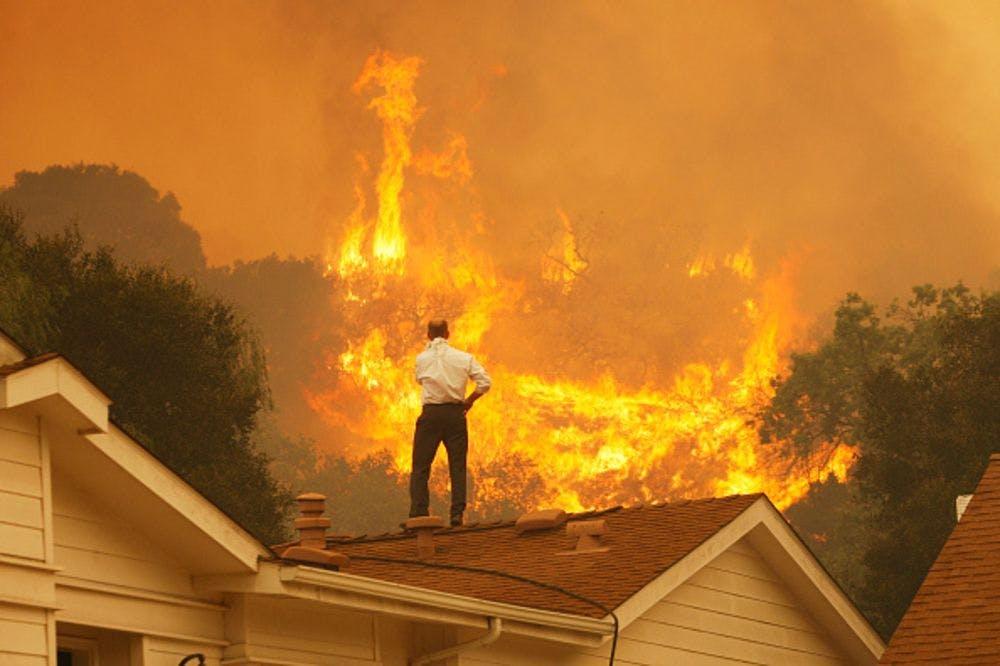 man roof burning house