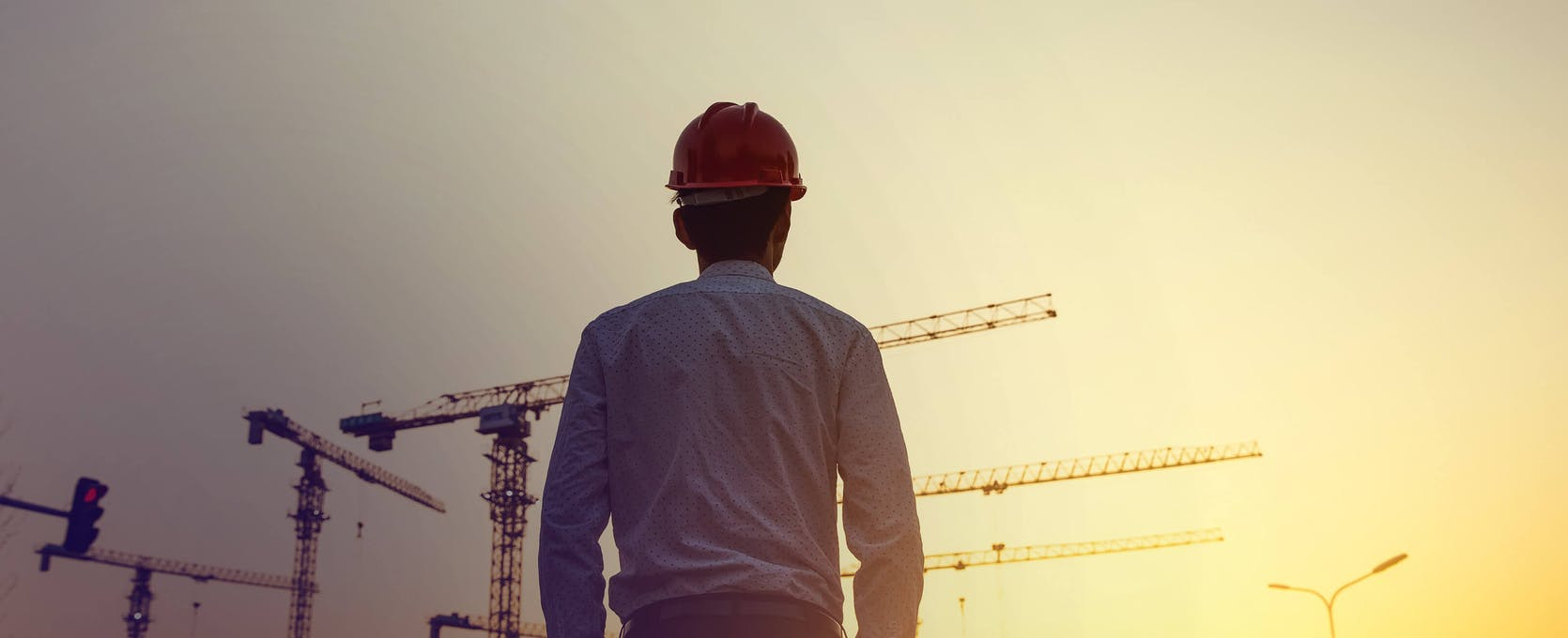 Man in a hard hat looking out at a construction site at sunset