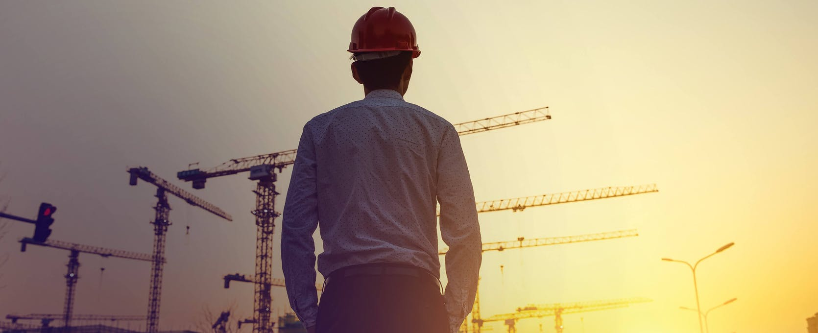 Contractor looks at construction site while considering project finance