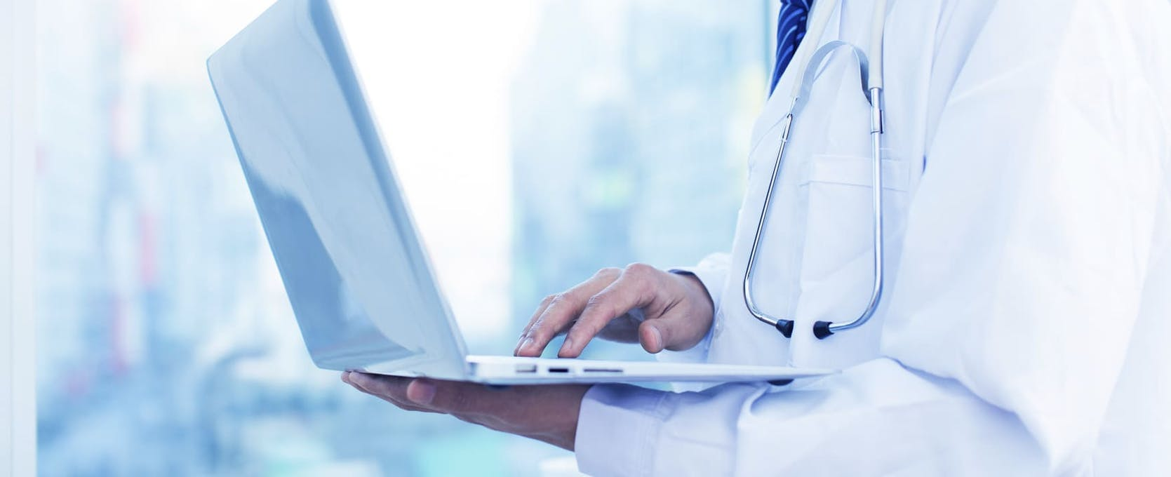 Doctor standing and working on a laptop