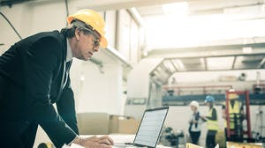 Man in hard hat working on a computer